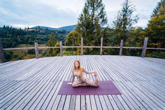 kvinde der dyrker yoga på terrasse